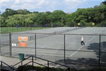 An adult participating in a tennis game on a multicourt facility
